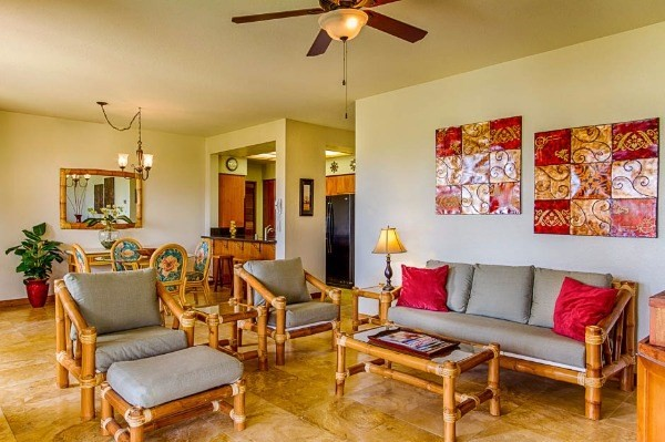 A well-placed Shores ground-floor condo with an unusually bright character combined with a large 2-bedroom layout.  Floors throughout the main living area are newly tiled in an attractive marble design; bedrooms maintain their soft, pristine carpeting.  Kitchen and bathrooms are freshly upgraded, with the tile along the tub and shower walls in the same slick motif as the living room floors.  The informal yet elegant style scheme merges wonderfully with the natural landscape.  Significant lanai, which features two sets of patio furnishings, is encircled by a liberal amount of open lawn space.  And there are lovely views of the golf fairways with scattered palms and the mountain slopes in the distance.  Situated closer to the main gate for ease of movement—with the Tropics restaurant, the Hilton, and the A-Bay beach trail reachable in minutes—though nevertheless a private and quiet unit.