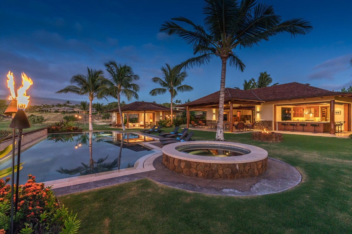 "One of the finest custom homes within the private and gated Kauna'oa at Mauna Kea community. This one level (no steps!), upscale, 6 bedroom 6.5 bath home is situated on an elevated 1.24 acre home site bordering the 13th fairway of the Mauna Kea Golf Course with ocean views overlooking the 12th fairway in addition to spectacular views of the Kauna'oa  private Par 3 golf course and the Kohala Mountain. The mid century modern design offers an open floor plan that is the epitome of indoor/outdoor living; even the kitchen totally opens to the yard and pool! The main living area includes a gourmet kitchen, expansive great room, laundry room, powder room and a home theater room, complete with a 90"" TV and surround sound. The separate master bedroom suite includes a wet bar, spacious bathroom and outdoor garden shower. The guest pavilion has 4 bedroom suites, one with built in bunk beds. Each bedroom suite has its own outdoor shower. The large, private yard area wraps around the over-sized swimming pool, complete with a water terrace, separate spa and gas fire pit. The property has been beautifully re-landscaped and includes three-car garage with an additional separate laundry, housekeeper/maids bedroom and bath. High-end custom finishes include motorized sun shades in the main pavilion, hardwood and stone floors, vaulted ceilings and mahogany pocket doors and trim throughout. Direct golf cart access or easy walk to Mauna Kea beach and hotel!Excellent registered vacation rental with potential for more revenue, as seller only rents the home 10-11 weeks per year for large amounts."