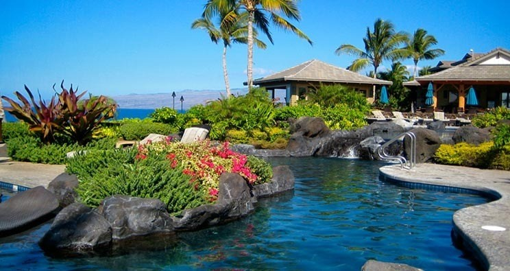 PRICE REDUCED $50,000! Don't miss this exceptional ground floor unit within the gated oceanfront community of Hali'i Kai located within the World Class Waikoloa Beach Resort on the Big Island of Hawaii. This 2 bedroom, 2 bath includes one parking spot PLUS individual garage parking. Conveniently located within a short walk to the pool/restaurant and offers walkout to golf course, ocean and sunset views set in green fields and lush tropical vegetation. It is a popular floor plan and includes granite counter tops, African mahogany cabinets, stainless steel appliances, tile flooring, central air, a covered lanai close to barbecue grill and hammocks. Hali'i Kai offers an upscale oceanfront club complete with large lagoo-style pool, open air workout facility and full service restaurant.