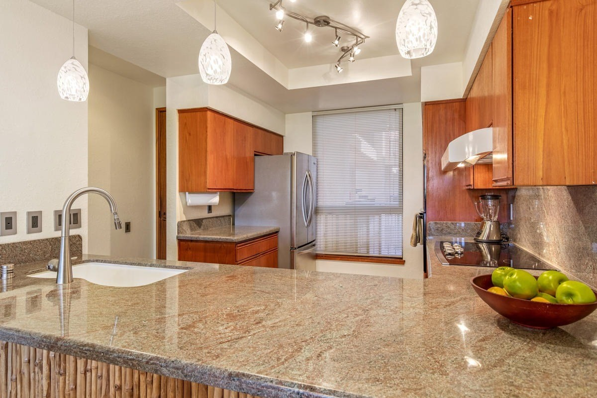 This spacious unit, located in the Bo Tree Tower has been tastefully remodeled and the location provides for tropical views with some ocean in the distance.  This is a great place to watch sunsets! Did we mention the bird's eye view of the koi ponds below which are unique to The Shores?  From the moment you step into Shores 232, you can't help but notice the cohesiveness of the space.  From the tasteful finishes in the kitchen (including granite countertops, light fixtures, faucet, cooktop, etc.) and the tile flooring throughout, to the wonderful bathroom remodels, there is a sense of calm.  The use of mirrors along an entire wall in the living room/dining room reflects the tropical surroundings and adds to the spacious feel of the place.  Step out onto the large L shaped lanai with wet bar and you'll find enough space for BOTH dining and relaxing in the chaise lounge chairs!  The view from this location is unique in that you are high enough up to enjoy the surrounding trees at eye-level, look down and see the koi fish in one of the ponds below and look out to watch palm trees swaying and the ocean beyond.  Shores 232 is being sold turnkey furnished.