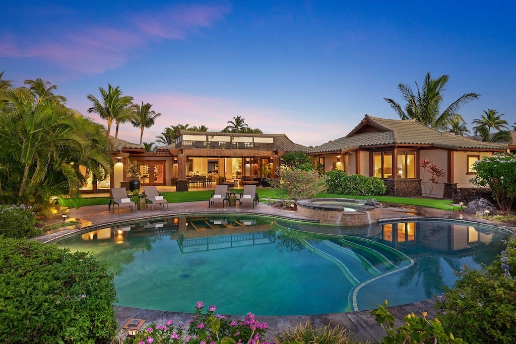 """Located in the prestigious private resort home community of Champion Ridge, this sprawling retreat offers four spacious bedrooms/five bathrooms and 360 degree views spanning the ocean, golf course and volcanic mountains. Champion Ridge 22 is constructed on a large private lot with three separate structures surrounded by large common area with lush tropical foliage. Located just a short drive to the Beach Club, golf course, grocery store and restaurants, Champion Ridge 22 is centrally located within the Mauna Lani Resort. Special features of the home include a huge covered outdoor lanai with new outdoor kitchen, and living space with a private pool, hot tub, and grass yard. Climb the spiral staircase up to the second floor sun deck and marvel at the views of the Pacific Ocean and Maui, and nightly sun sets.Champion Ridge 22 is designed with high-end finishes, stone floors and new furnishings purchased in December of 2014. The main hale (house) is comprised of a large chefs kitchen, open-concept dining/living area and an en-suite master bedroom.  Some new appliances purchased in August 2019.  The grand master bedroom is it's own separate hale, also referred to as the """"honeymoon suite"""", and boasts a luxurious bathroom with a jetted bath and tropical outdoor shower. A third hale offers 2 private bedrooms, each with their own bathroom. There are king size beds in three out of the four bedrooms and a queen size bed in the fourth bedroom. The furnishings were carefully selected with bright fun colors.  The property has been extremely well maintained with $200,000 spent with interior and exterior paint, new 3 new air conditioning units, new appliances, updated exterior cabinetry and tile work and new furniture throughout.Champion Ridge is a gated, residential community with a manicured park area complete with fruit trees and herb garden."""